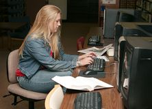 Studying young adult. One young female student studying in a college library Royalty Free Stock Image