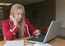 Studying young adult. One young female student studying in a college library Stock Photos