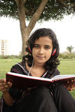 Studying. Young beautiful student reading book and listening music Royalty Free Stock Photography