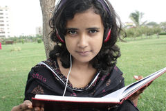 Studying. Young beautiful student reading book and listening music Royalty Free Stock Photos