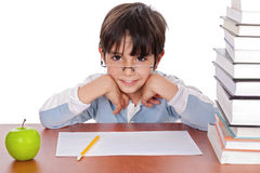 Studying young boy gives strange. Look wearing specs over isolated background Royalty Free Stock Photography