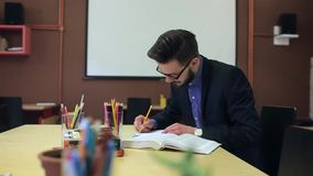 Studying of a young man, rewrites a notebook stock footage