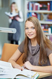 Young student girl working with book in library Stock Photos