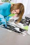 Stufa di pulizia della giovane donna in cucina immagini stock libere da diritti