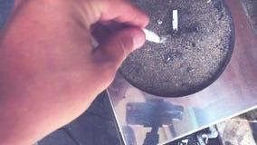 Stufato della mano dell'uomo una sigaretta in un portacenere fuori Isola di Bali video d archivio