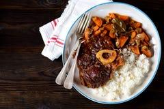Stufato di manzo di ossobuco con riso bollito in salsa al pomodoro con le foglie delle cipolle, delle carote, del sedano, dell'ag Fotografia Stock