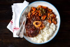 Stufato di manzo di ossobuco con riso bollito in salsa al pomodoro con le foglie delle cipolle, delle carote, del sedano, dell'ag Immagine Stock