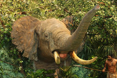 Stuffed african elephant against lifelike jungle with hunter Stock Photo