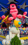 Stuffed Animal Prizes. An oversized stuffed pink gorilla and a large stuffed dog sit alongside an amusement park game at the 2014 Wisconsin State Fair Royalty Free Stock Images