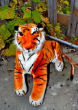 Stuffed animal tiger toy in garden. Stuffed animal tiger toy domineering expression doll in garden stock photos