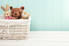 Stuffed animal toys. In a basket on the floor. A turquoise wainscot