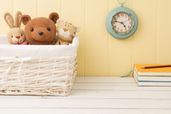 Stuffed animal toys in the school. Stuffed animal toys in a basket and a blue clock on the wainscot. Some notebooks and a pencil. Back to school Stock Photo