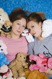 Stuffed Animals. Young women surrounded by stuffed animals on bed Stock Images