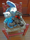 Stuffed animals sitting in a hand painted chair Stock Photos