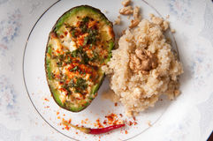 Stuffed avocado dish. Stuffed avocados with walnut red pepper and quinoa garnish in porcelain plate royalty free stock image