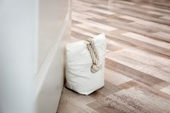 Stuffed bag holding wooden door. At home royalty free stock photos