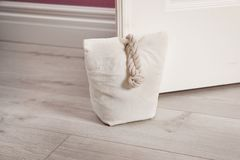 Stuffed bag holding wooden door. At home stock photo