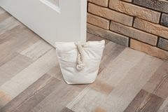 Stuffed bag holding wooden door. At home stock image