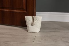 Stuffed bag holding wooden door. At home stock photography