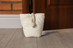 Stuffed bag holding wooden door. At home stock images