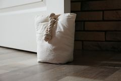 Stuffed bag holding wooden door. At home royalty free stock photo