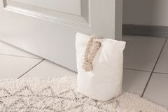 Stuffed bag holding wooden door. At home stock photos