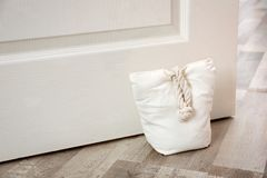 Stuffed bag holding wooden door. At home royalty free stock photography