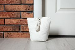 Stuffed bag near white door. At home stock images