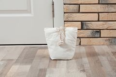 Stuffed bag near white door. At home stock photo