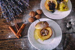 stuffed baked apple with nuts, honey and chocolate on white dessert plates, dark wooden background. Christmas sweet. healthy eatin Stock Photography
