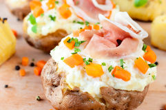 Stuffed baked potato. Baked and stuffed potato with vegetables and cheese cream Stock Images