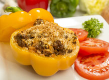 Stuffed bell pepper. With beef and rice topped with parmesan cheese and garnished with sliced tomatoes and parsley stock image