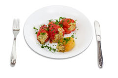Stuffed bell peppers on a white dish, fork and knife Stock Photos