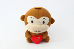 Stuffed brown monkey holding a red heart. Stock Image