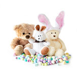 Stuffed buddies and candy. Toy bunnies  and bear are stuffed buddies. isolated on a white background with chocolate easter eggs in pastel colors Stock Image