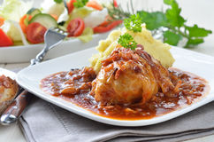 Stuffed cabbage. Cabbage rolls, stuffed with minced meat; as garnish purree, salad and a toasted slice of baguette with bacon Royalty Free Stock Photo