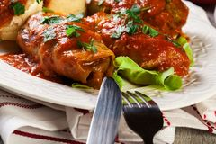 Stuffed cabbage with meat and rice served with boiled potatoes and tomato sauce Stock Photo