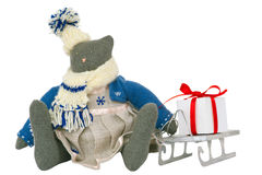 Stuffed cat toy in dress, sled with present nearby. Stuffed tabby-cat toy in dress sits with decorated gift box on a sled nearby. Decoration for Christmas Royalty Free Stock Image
