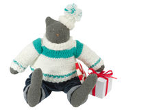 Stuffed cat toy in pants with a gift box alongside. Stuffed tomcat toy in pants sits with a gift box alongside. Decoration for Christmas. Isolated on white Royalty Free Stock Photo