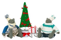 Stuffed cat toys in pants and dress with fir tree. Two stuffed cat toys in pants and dress sitting with fir tree and sled with gift box nearby. Decoration for Stock Photography