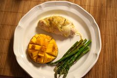 Stuffed chicken, mango, and asparagus low carb dinner. Can be visually appealing as well as healthy and delicious. Cut the mango into geometric cubes and stock image
