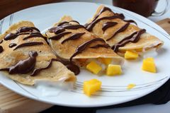 Stuffed crepes with mango, vegetal yogurt and chocolate. Stuffed crepes with mango, vegetal yogurt and chocolate on a white plate royalty free stock photos