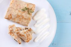Stuffed crepes topped with sour cream Stock Photo