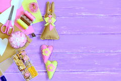 Stuffed Easter bunny with hearts made from felt. Scissors, pins, thread spools, thimble, buttons and beads in box, colorful felt Royalty Free Stock Photo
