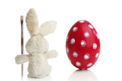 Stuffed Easter bunny paints a red Easter egg Stock Photos
