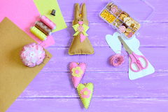 Stuffed Easter bunny toy with hearts sewn from felt. Scissors, pins, thread, thimble, buttons and beads in box, paper template. Tools and materials for kids Stock Image
