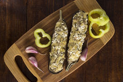 Stuffed eggplant dish on a boards on the kitchen table with garlic and sweet pepper Royalty Free Stock Image
