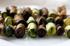 Stuffed eggplant and zucchini rolls. On wooden skewer on white plate Stock Image