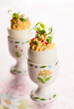 Stuffed eggs in egg cups Stock Photo