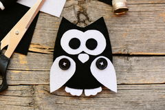 Stuffed felt owl ornament on a vintage wooden background. Making adorable owl ornament from black and white felt. DIY felt project. Things to make with felt Royalty Free Stock Photos